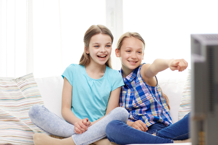 people, children, television, friends and friendship concept - two happy little girls watching tv and pointing finger at home