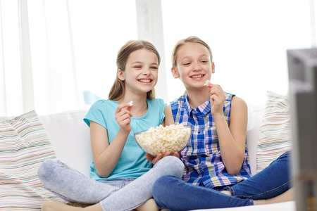 people, children, television, friends and friendship concept - two happy little girls watching comedy movie on tv and eating popcorn at home Banco de Imagens