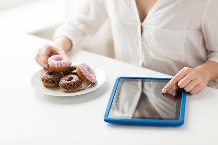 unhealthy diet: people, junk food, diet, technology and unhealthy eating concept - close up of hands with tablet pc computer and donuts counting calories and sitting at table at home