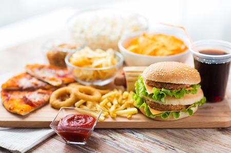 fast food and unhealthy eating concept - close up of hamburger or cheeseburger, deep-fried squid rings, french fries, drink and ketchup on wooden table Archivio Fotografico
