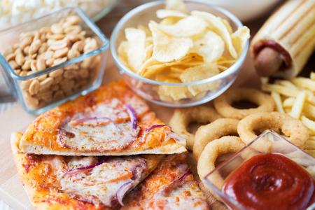 ファーストフードや不健康な食事の概念 - は、ピザ、揚げイカリング、ポテトチップス、ピーナッツ、木製テーブル トップ ビューでケチャップのク