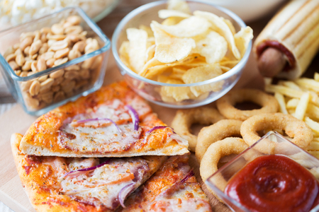 fast food and unhealthy eating concept - close up of pizza, deep-fried squid rings, potato chips, peanuts and ketchup on wooden table top view 版權商用圖片