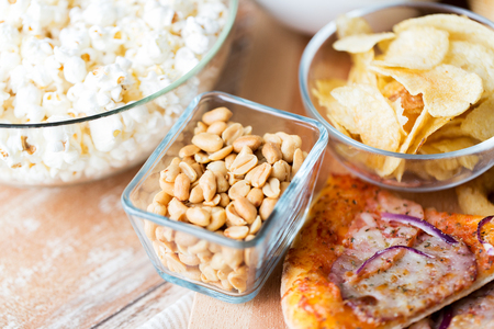 bowl of popcorn: fast food and unhealthy eating concept - close up of peanuts in glass bowl, potato chips, pizza and popcorn on wooden table Stock Photo