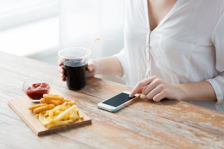 diet food: fast food, people, technology and diet concept - close up of woman with smartphone drinking cola and eating french fries, ketchup and deep-fried squid rings at wooden table Stock Photo