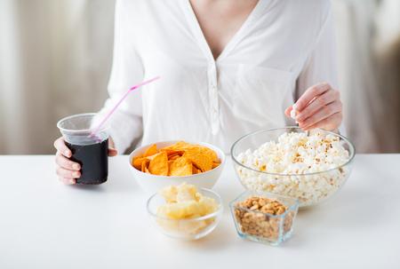 comida chatarra: la gente, la comida rápida, comida basura y el concepto de alimentación poco saludable - cerca de la mujer con palomitas, nachos o patatas fritas de maíz y cacahuetes en cuencos