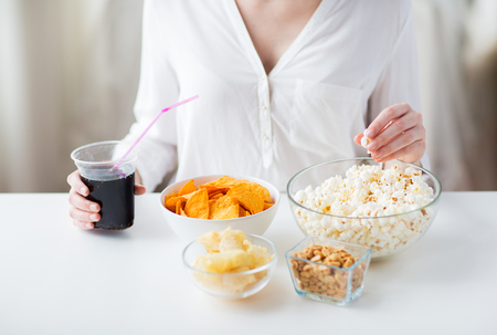 people, fast food, junk-food and unhealthy eating concept - close up of woman with popcorn, nachos or corn crisps and peanuts in bowls