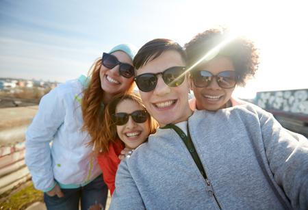 adolescente: turismo, viaje, gente, ocio y concepto de la tecnología - grupo de amigos sonrientes adolescentes que están tomando autofoto en la calle de la ciudad