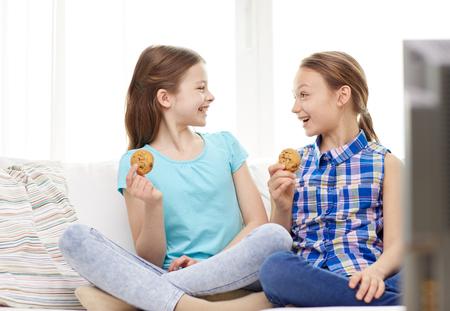 mensen, kinderen, televisie, vrienden en vriendschap concept - twee gelukkige meisjes tv kijken en het eten van cookies thuis