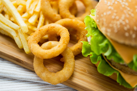 fast food restaurant: fast food, junk-food and unhealthy eating concept - close up of hamburger or cheeseburger, deep-fried squid rings and french fries on wooden table