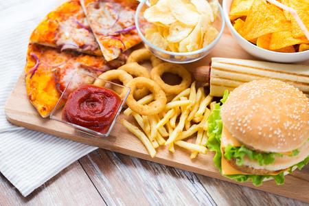 HAMBURGUESA: comida rápida y el concepto de alimentación poco saludable - cerca de la hamburguesa o hamburguesa, anillos de calamar fritos, patatas fritas, pizza y salsa de tomate en la mesa de madera vista desde arriba