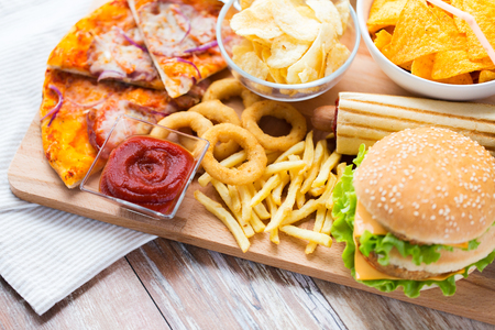 fast food and unhealthy eating concept - close up of hamburger or cheeseburger, deep-fried squid rings, french fries, pizza and ketchup on wooden table top view Imagens