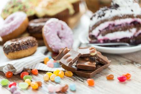 jelly beans: junk food, sweets and unhealthy eating concept - close up of chocolate pieces, jelly beans, glazed donuts and cake on wooden table