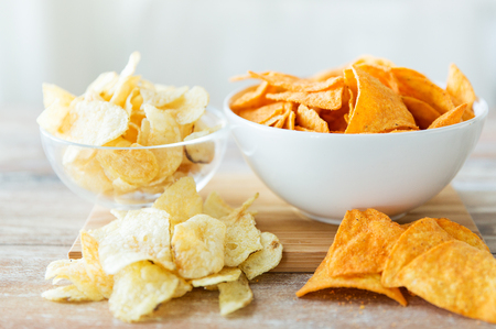 crisps: fast food, junk-food, cuisine and eating concept - close up of crunchy potato crisps and corn crisps or nachos in bowls