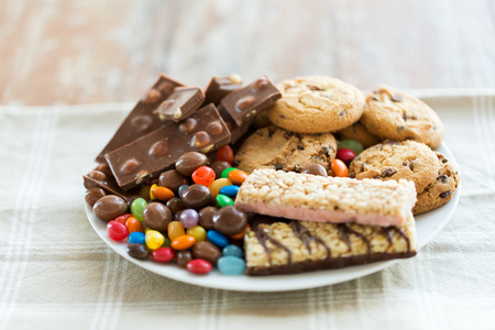 galletas: comida chatarra, dulces y poco saludable concepto de alimentaci�n - cerca de chocolate, galletas de avena, caramelos y barritas de muesli en placa Foto de archivo