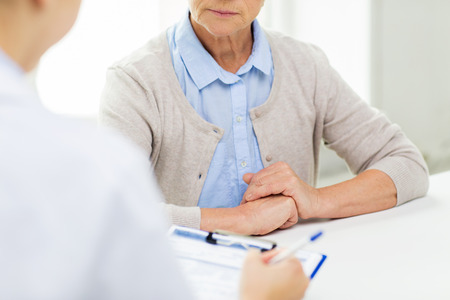 medicine, age, health care and people concept - close up of senior woman and doctor hands with clipboard meeting in medical office Banque d'images