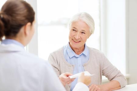 医学、年齢、医療、人々 コンセプト - 医師の病院で満足している年配の女性に処方を与える
