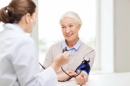 medicine, age, health care and people concept - doctor with tonometer checking happy senior woman blood pressure level at hospital