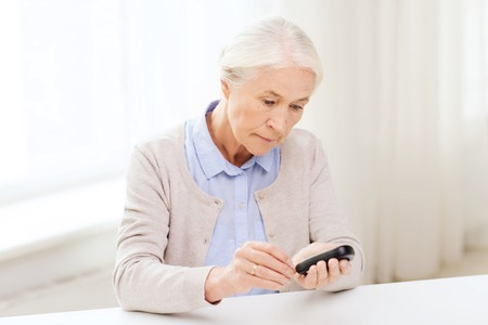 blood sugar: medicine, age, diabetes, health care and people concept - senior woman with glucometer checking blood sugar level at home