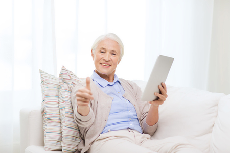 computer age: technology, age, gesture and people concept - happy senior woman with tablet pc computer showing thumbs up at home