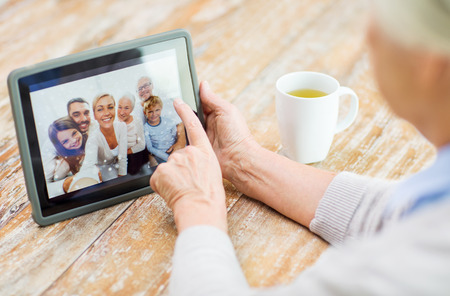 vejez feliz: tecnología, la edad, los recuerdos y las personas concepto - mujer feliz altos con la visualización de la computadora tablet pc familia álbum de fotos en casa
