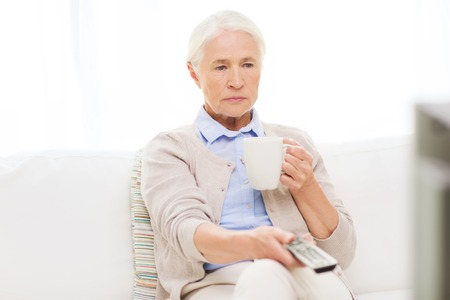changing channels: technology, television, age and people concept - senior woman watching tv, drinking tea and changing channels by remote control at home Stock Photo