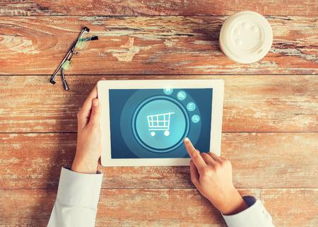 비즈니스, 사람, 온라인 쇼핑 및 기술 개념 - 가까운 트롤리 아이콘, 커피 컵과 테이블에 안경과 태블릿 pc 컴퓨터 화면에 손가락을 가리키는 손 최대