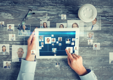 INTERNATIONAL BUSINESS: negocio, la gente, la comunicación internacional, headhunting y tecnología concepto - cerca de las manos apuntando el dedo a la pantalla del ordenador Tablet PC con la red mapa del mundo e internet contactos en la mesa