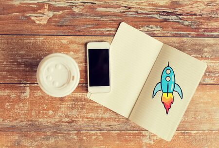 smartphone: business, education, objects and technology concept - close up of coffee paper cup, smartphone and rocket drawing in notebook on table Stock Photo