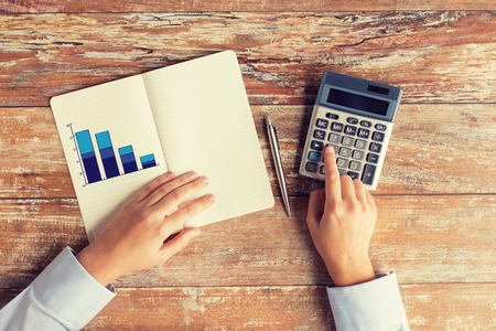 calculadora: negocio, la educación, las personas y la tecnología concepto - Cierre de manos femeninas con calculadora, lápiz y gráfico de dibujo en el cuaderno en la mesa
