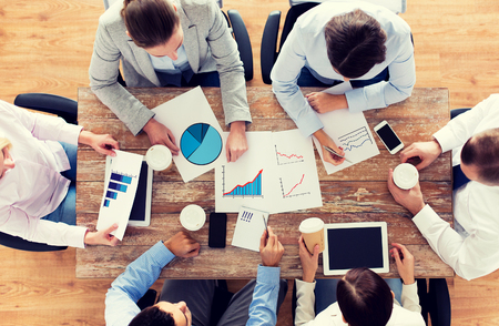 business, people, statistics and team work concept - close up of creative team with charts and gadgets meeting and drinking coffee in office. Stock Photo