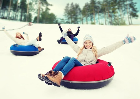 tubes: winter, leisure, sport, friendship and people concept - group of happy friends sliding down on snow tubes