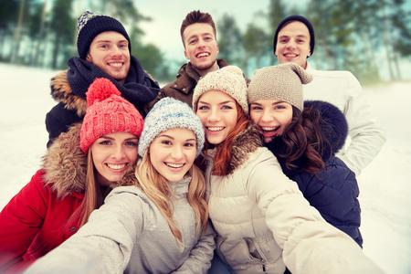 ropa de invierno: invierno, la tecnología, la amistad y el concepto de la gente - grupo de sonriente de hombres y mujeres teniendo Autofoto aire libre Foto de archivo