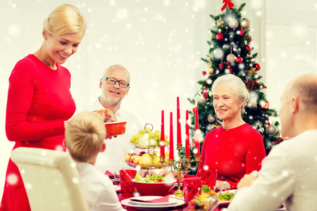 christmas meal: family, holidays, generation, christmas and people concept - smiling family having dinner at home