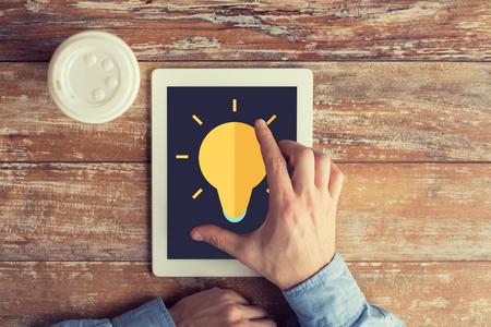 inspiracion: negocios, la educaci�n, la inspiraci�n, la gente y la tecnolog�a concepto - Cerca de las manos masculinas con el icono de la bombilla de luz en la pantalla del ordenador Tablet PC y la taza de caf� en la mesa