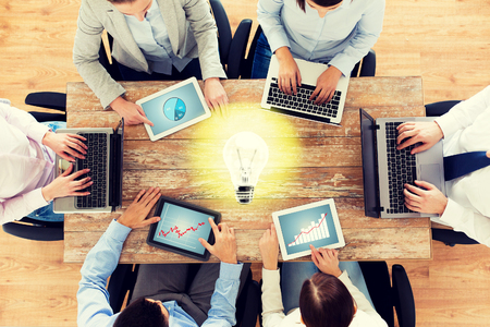 group of persons: business, people and technology concept - close up of creative team with laptop and tablet pc sitting at table in office over lighting bulb