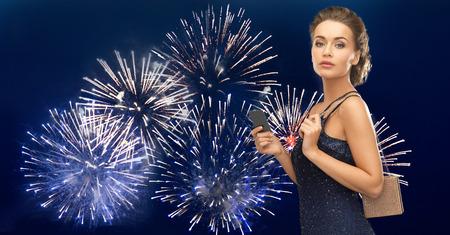 anochecer: la gente, el lujo, la vida nocturna y el concepto de finanzas - hermosa mujer en traje de noche con la tarjeta vip y bolsa en fuegos artificiales sobre fondo azul oscuro