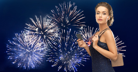 christmas party: people, luxury, night life and finance concept - beautiful woman in evening dress with vip card and bag over firework on dark blue background