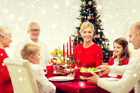 familie, vakantie, generatie, kerst en de mensen concept - lachende familie die diner thuis