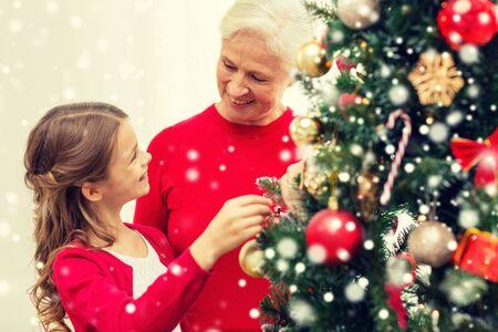 arbol genealógico: concepto de familia, las vacaciones, la generación y la gente - sonriente niña con la abuela decorar el árbol de Navidad en casa