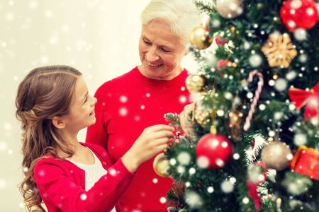 decorating christmas tree: family, holidays, generation and people concept - smiling girl with grandmother decorating christmas tree at home Stock Photo