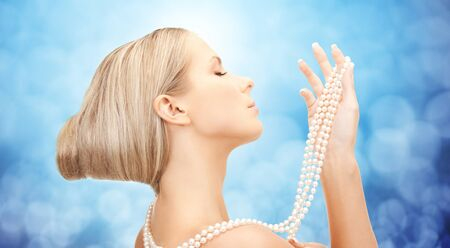 pearl necklace: beauty, luxury, people, holidays and jewelry concept - beautiful woman with sea pearl necklace or beads in hand over blue lights background