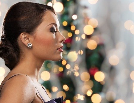 diamond: people, holidays, jewelry and luxury concept - woman face with diamond earring over christmas tree lights background Stock Photo