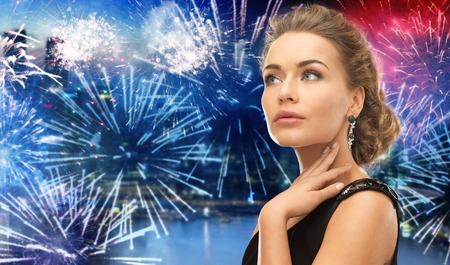 사람, 휴일 및 매력적인 개념 - 밤 도시 배경에서 불꽃 놀이 통해 귀걸이 입고 아름 다운 여자