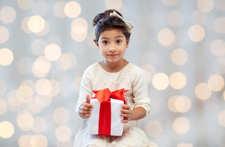 asian child: holidays, presents, christmas, childhood and people concept - smiling little girl with gift box over lights background Stock Photo