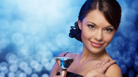 cocktail dress: party, drinks, holidays, luxury and celebration concept - smiling woman in evening dress holding cocktail over blue lights background