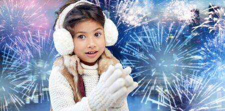 asian style: winter, holidays, children and people concept - happy little girl wearing earmuffs over firework background
