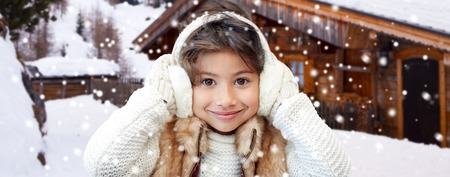 niños sonriendo: vacaciones de invierno, estación, navidad, la gente y el concepto de los niños - niña que llevaba guantes y orejeras felices sobre el fondo de la casa de campo de madera y la nieve Foto de archivo