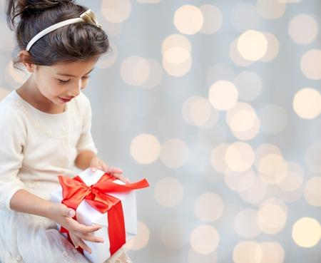 felicitaciones cumpleaÑos: días de fiesta, los presentes, navidad, la infancia y concepto de la gente - una sonrisa de niña con caja de regalo sobre fondo de las luces