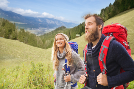 adventure holiday: adventure, travel, tourism, hike and people concept - smiling couple walking with backpacks over natural landscape background
