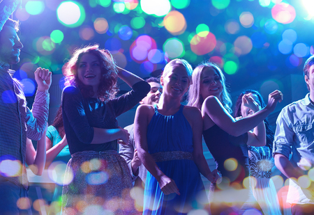 party night: party, holidays, celebration, nightlife and people concept - group of happy friends dancing in night club